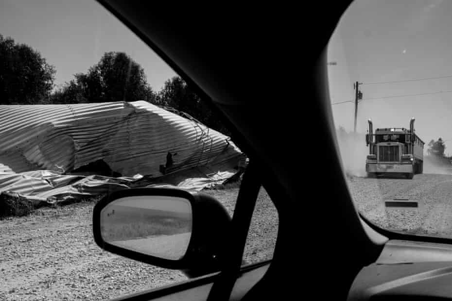 A semi truck drives past a destroyed silo in Atkins, Iowa.
