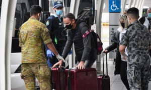 Passengers hand over their luggage in order to enter hotel quarantine off a flight from Melbourne at Sydney International Airport.