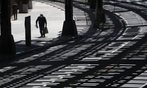 A man wearing a mask walks beneath elevated subway tracks on a Brooklyn street