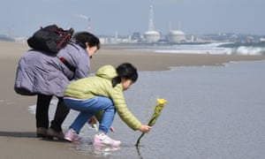A girl and her grandmother place flowers in the sea in Sendai