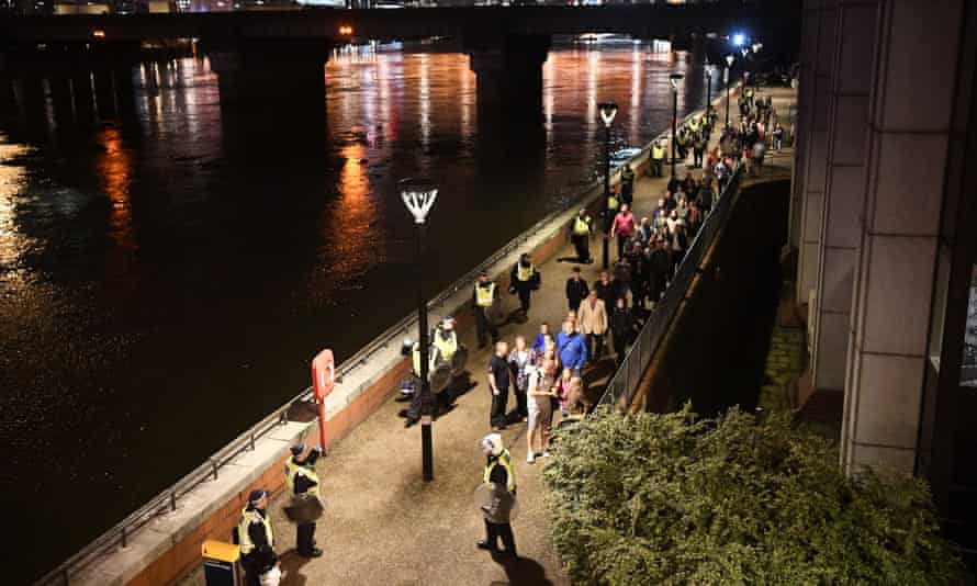 People are lead to safety away from London Bridge on Saturday night in London.