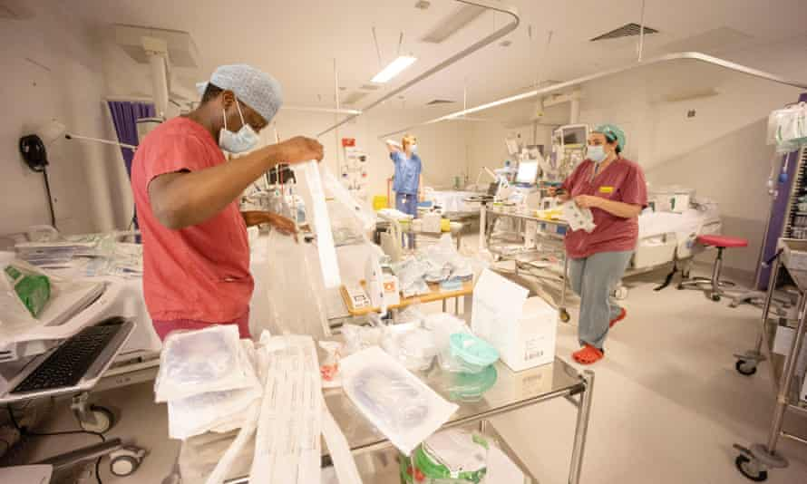 Hospital staff spend New Year's Eve turning surgical theatres and recovery departments into intensive care wards for the influx of Covid-19 patients.