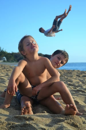 Two boys on the beach on the west side of Reunion island at L'Hermitage-les-Bains, as an acrobatic photo-bomber behind them tumbles on the sand.