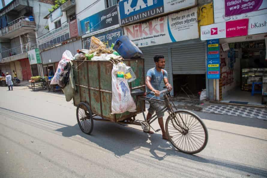 A man pushes a waste-laden rickshaw along a street