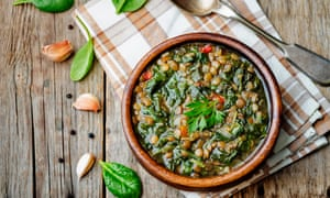 Lentil spinach soup on a dark wood background