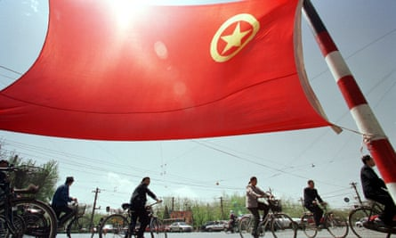 Cyclists pass by the flag of China's Communist Youth League in Beijing. Up to 10 million members are expected to go to rural areas by 2022.
