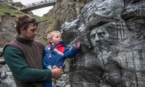 A young boy looks at a carving of Merlin at Tintagel Castle in Tintagel