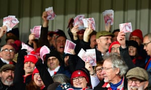 Gloucester fans wave fake £50 notes at the start of the game.