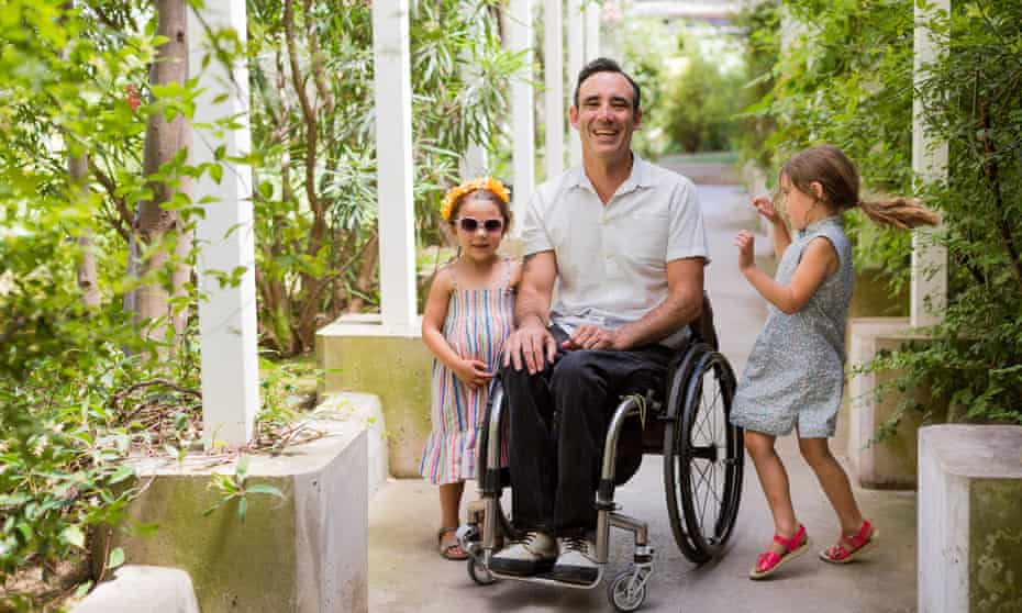 'My wheelchair is a part of me, my life would be significantly poorer without it.' Jarred McGinnis with his daughters Poe (right) and Hedy Lu.