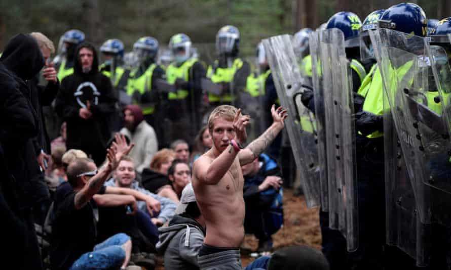 A reveller puts his hands up in front of riot police at the scene of a rave in Thetford forest, Norfolk.
