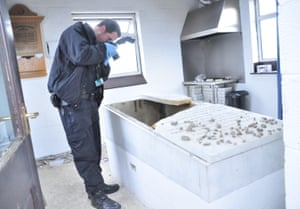 A GMP crime scene officer takes pictures in the prayer hall at the cemetery in Whitefield