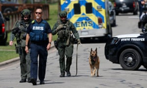 Police walk through a Pflugerville neighborhood as the FBI investigates the home of Austin bombing suspect Mark Conditt.