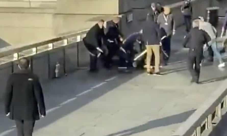 Steve Gallant, in the centre wearing a purple jumper, is crouched over the terrorist Usman Khan on London Bridge.