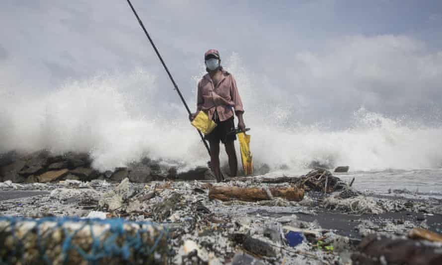 A man fishes on a beach covered with plastic pellets