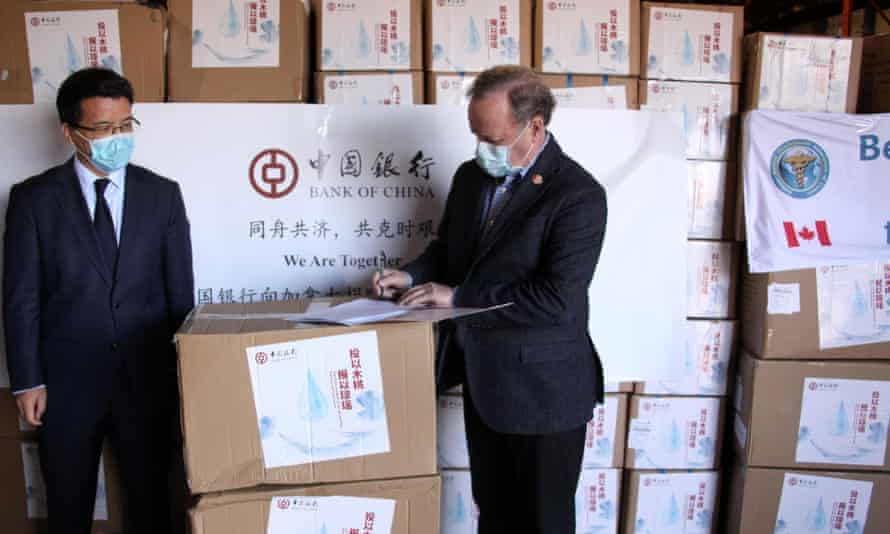 Li Aihua, president of Bank of China (Canada), poses with Lee Errett, a Canadian official, in front of boxes of Chinese medical supplies in Toronto. The Bank of China donated 7.5 tonnes of medical supplies to Canada.