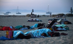 People camp and sleep on the beach in Bormes-les-Mimosas at sunrise on Thursday.
