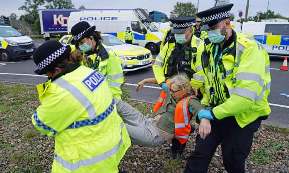 Police officers carry away one of a number of protesters who had glued themselves to the highway near junction 4 of the A1(M) near Hatfield, Hertfordshire