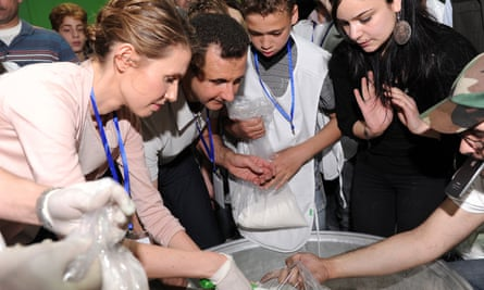 Bashar al-Assad and his wife, Asma, help pack aid supplies with volunteers at a food distribution centre in Damascus.