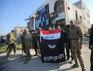 Iraqi security forces hold an Iraqi flag over an Isis flag