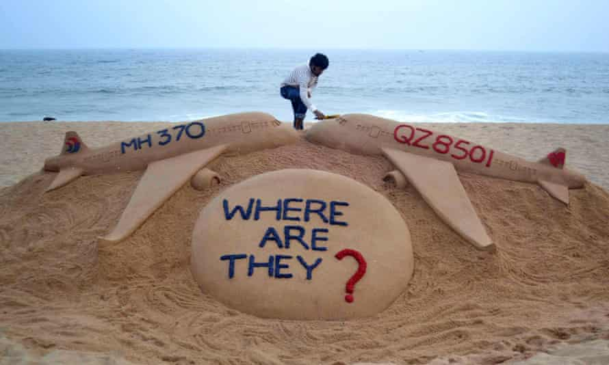 Indian sand artist Sudarsan Pattnaik gives the final touches to his sand sculpture portraying two missing aircraft, Air Asia QZ8501 and Malayasia Airlines MH370.
