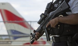 An armed British police officer patrols outside of Heathrow Airport in August 2006