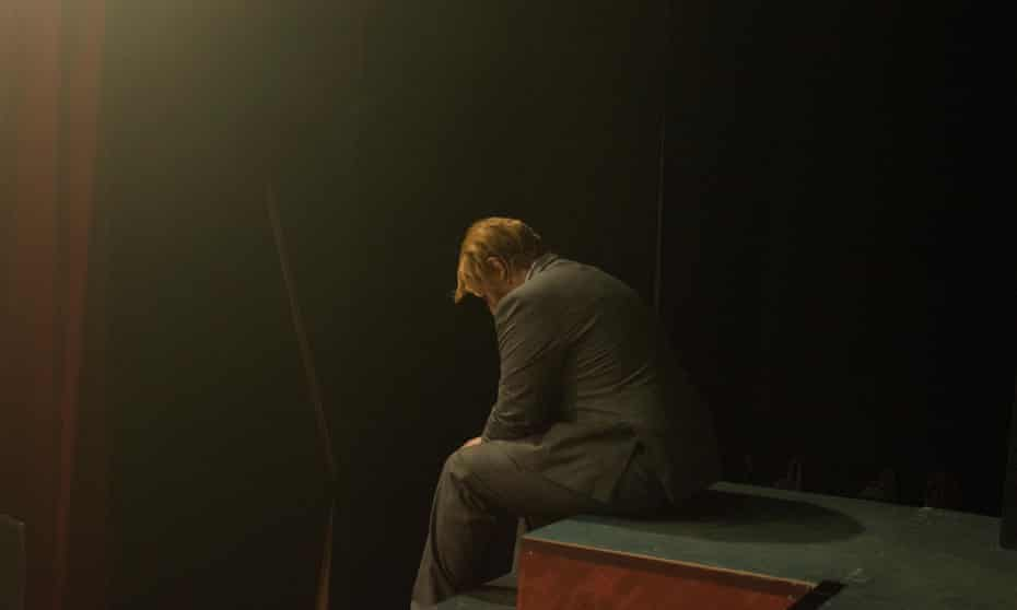 A man sits hunched in despair