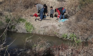 A man from Honduras and a woman and her children from Guatemala put on dry clothes after crossing part of the Rio Grande as they prepare to turn themselves over to US border patrol, on 13 January.