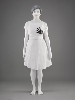 woman in white with black handprint on her breast