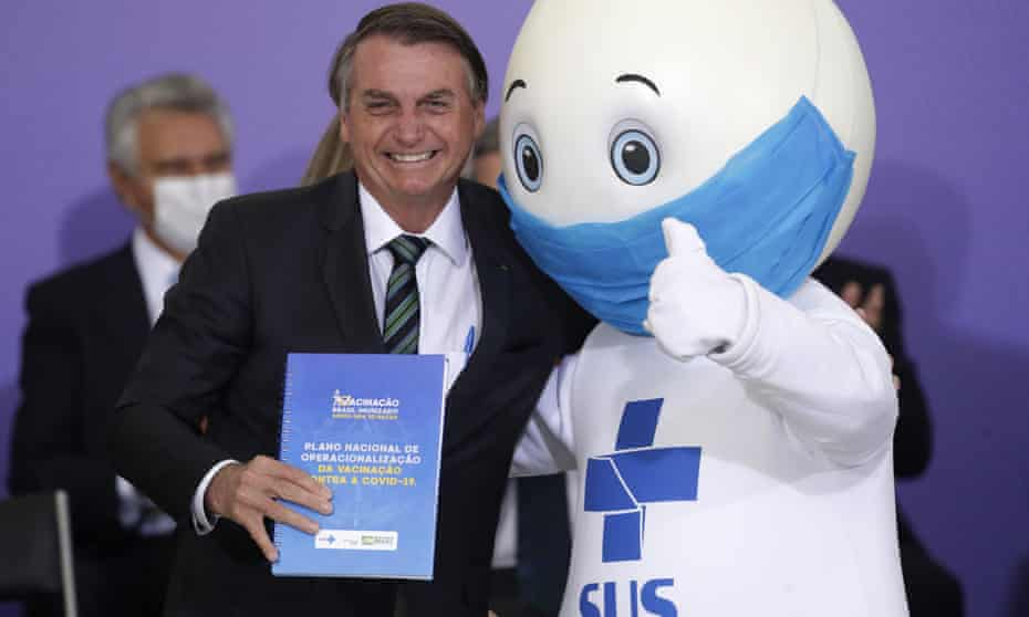President Jair Bolsonaro with 'Ze Gotinha', the mascot of the nation's vaccination campaign, during a ceremony to present Brazil's national vaccination plan against Covid in December.