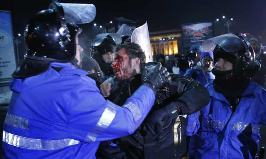 A wounded young man is arrested by riot police during a protest in front of government headquarters in Bucharest.