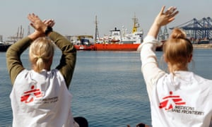 Two women wearing Médecins Sans Frontières T-shirts wave to the Aquarius relief ship in the port of Valencia, Spain