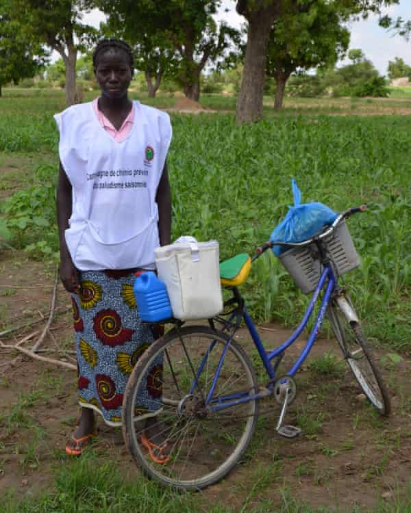 A community health worker distributes malaria drugs in Burkina Faso, where malaria accounts for about half of doctor visits.