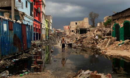 A woman walks along a street lined with rubble from buildings that collapsed in the earthquake in downtown Port-au-Prince