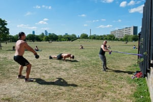 Three people work out in Burgess Park, south London, in May