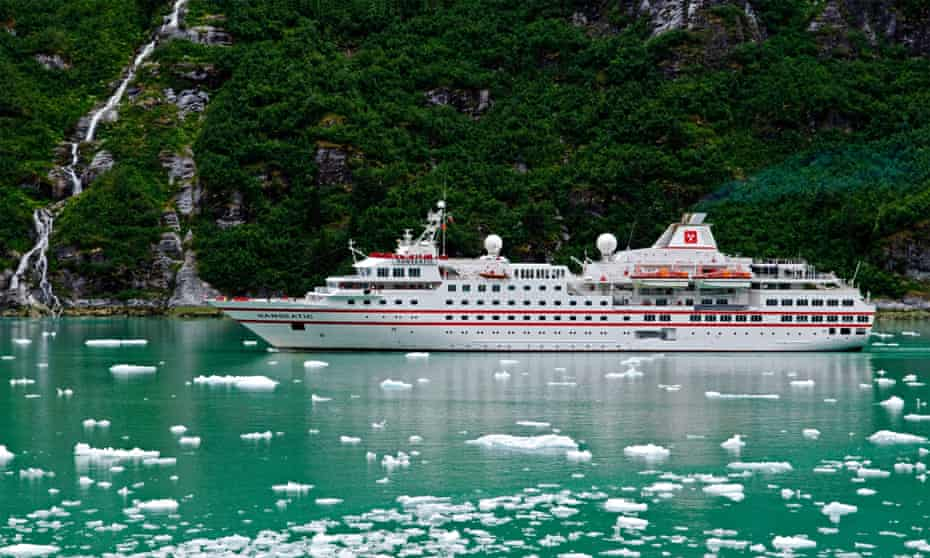 A cruise ship drifts by ice fragments amid a green-blue sea in Alaska, US