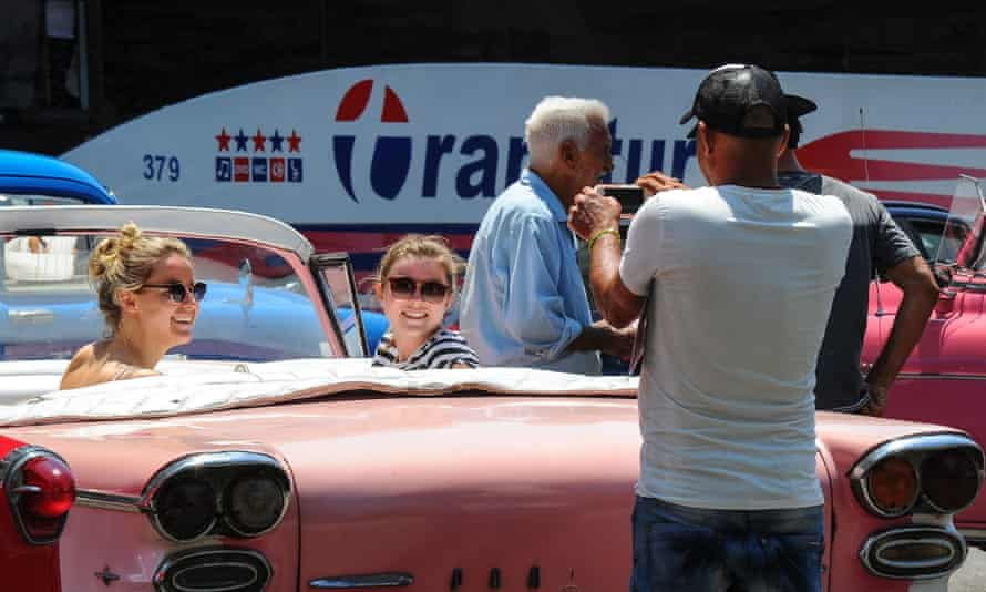 Tourists from the US pose in an old American car in Havana.