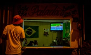 A man stops to watch the Olympic games on a TV screen at a bar in the Vidigal favela in Rio.