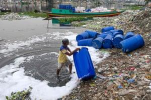 Dhaka, BangladeshA worker cleans barrels used to contain chemicals in Buriganga River