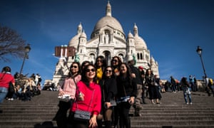 Tourists take selfies in front of the Sacre Coeur basilica, Paris.