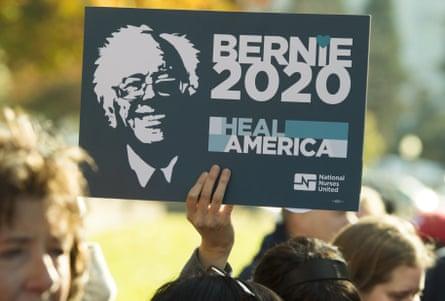 "A supporter of US Senator Bernie Sanders holds up a ""Bernie 2020"" sign"