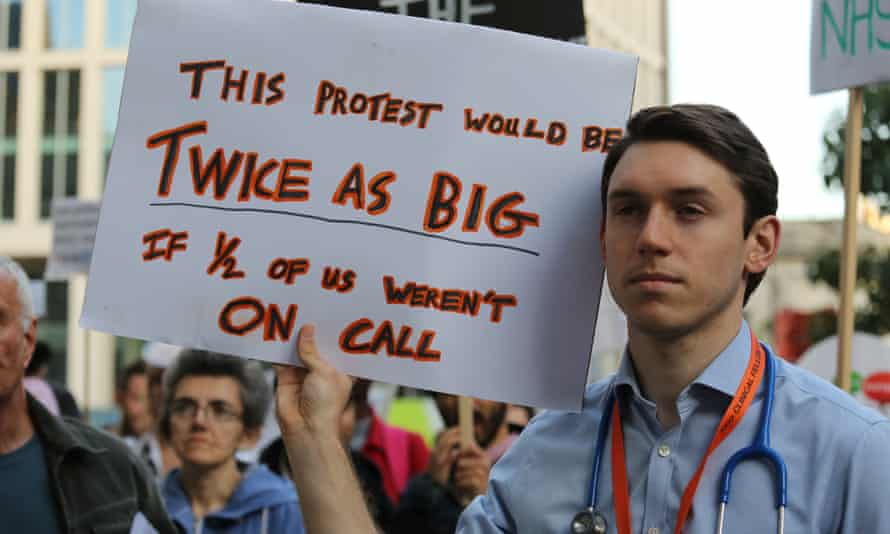 A junior doctor holds a placard during a demonstration in Manchester over changes to junior doctors' contracts.