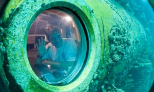 Fabien Cousteau waves from inside Aquarius Reef Base, a laboratory 63 feet below the surface in the waters off Key Largo, Florida in 2014