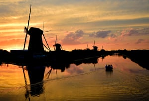 Kinderdijk, Netherlands People sail on a small ball at sunset next to windmills