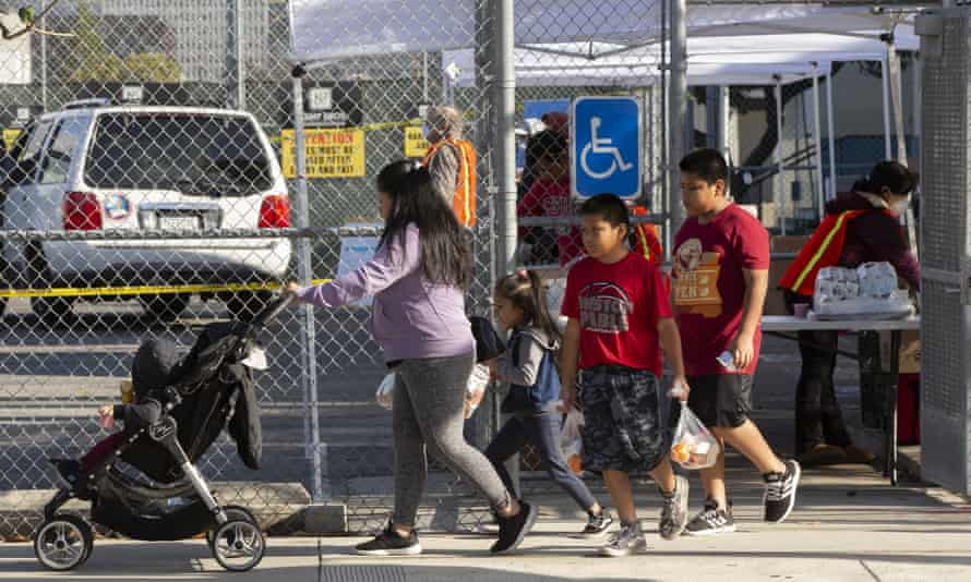 A family picks up free meals provided by the Los Angeles Unified school district at the Berendo middle school station in Los Angeles, in March.