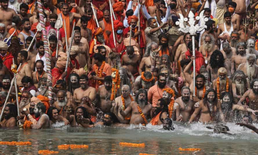 Naked Hindu holy men take holy dips in the Ganges River during Kumbh Mela, or pitcher festival, one of the most sacred pilgrimages in Hinduism, in Haridwar, northern state of Uttarakhand, India, Monday, April 12, 2021. They believe that a dip in holy water will wash away their sins and prevent rebirth. One prominent Hindu religious leader died of COVID-19. India has been overwhelmed by hundreds of thousands of new coronavirus cases daily, bringing pain, fear and agony to many lives as lockdowns have been placed in Delhi and other cities around the country. (AP Photo/Karma Sonam)