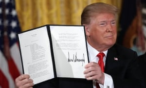 Donald Trump holds up an executive order to establish the space force, an independent and co-equal military branch.