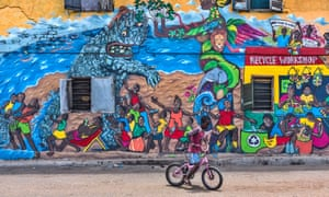 'Prepare not to sleep': a boy rides his bike past a mural by Barbara Siebenlist decorating the side of a building on Brazil Lane in Jamestown.