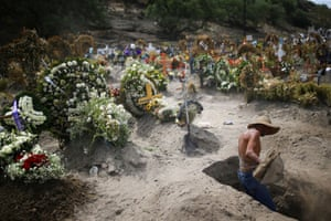A worker digs graves at the Xico cemetery on the outskirts of Mexico City, Mexico