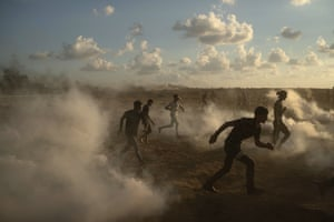 Palestinian protesters run from teargas fired by Israeli troops during a protest at the border with Israel.