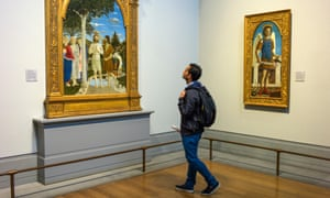 A visitor looks at Piero della Francesca's Baptism of Christ at the National Gallery, London.